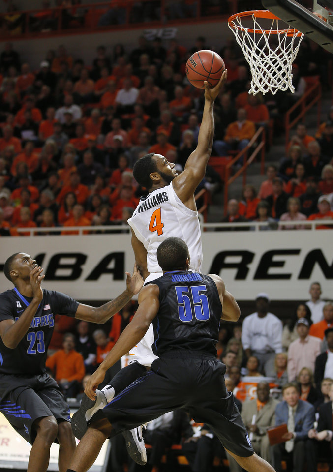 Photo - Oklahoma State's Brian Williams (4) goes to the basket past Memphis' Shaq Goodwin (23) and Geron Johnson (55) during an NCAA college basketball game between Oklahoma State and Memphis at Gallagher-Iba Arena in Stillwater, Okla., Tuesday, Nov. 19, 2013. Photo by Bryan Terry, The Oklahoman