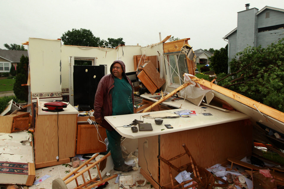 Photo - Wilburn Shaw looks for personal items in the remains of his kitchen in his home on Saturday, June 1, 2013, after Friday night's storm that passed through St. Charles, Mo., area.  The storm toppled cars and left commuters trapped on an interstate highway as it bore down during Friday's evening rush hour near Oklahoma City. The National Weather Service reported
