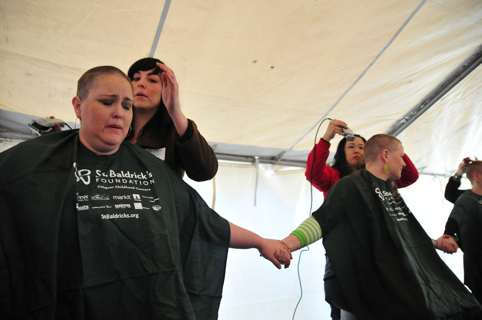 Jordan Keith, left, holds the hand of Beth McDowell, both members of the 10 Strong team, as they get their heads shaved for the St. Baldrick's charity at VZD's Restaurant and Club in Oklahoma City, Okla. Sunday, March 23, 2013.  Photo by Nick Oxford, for The Oklahoman