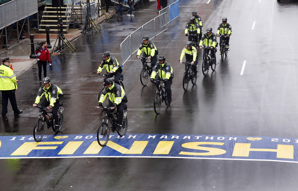 Photo - Police on bikes cycle across the Boston Marathon finish line prior to a remembrance ceremony for family members and survivors of the 2013 Boston Marathon bombing on Boylston Street in Boston, Tuesday, April 15, 2014. (AP Photo/Elise Amendola)