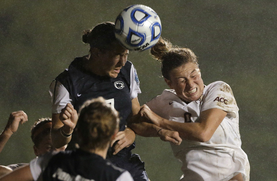 Photo - Florida State's Kassey Kallman, right, and Penn State's Whitney Church go for a head ball during the second half in an NCAA women's college soccer tournament semifinal, Friday, Nov. 30, 2012, in San Diego. Penn State won 2-1 in overtime. (AP Photo/Gregory Bull)