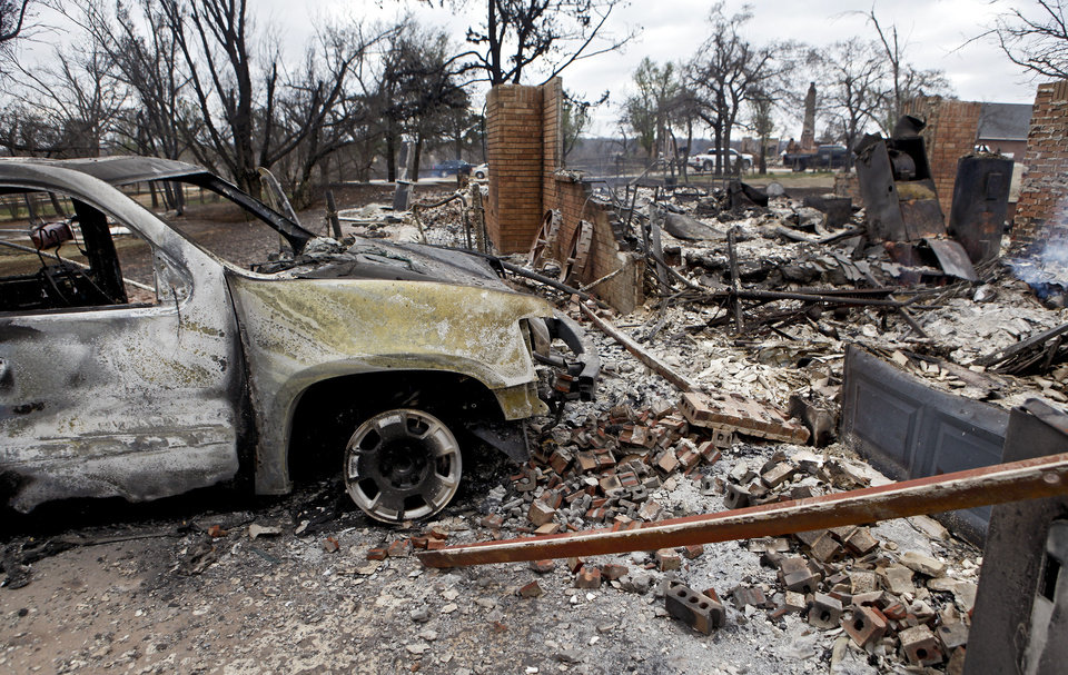 Photo - A burned out truck sits in the driveway of a house that was destroyed by wildfires near Reno Avenue and Hiawassee Road on Friday, April 10, 2009, in Midwest City, Okla.  Photo by Chris Landsberger, The Oklahoman