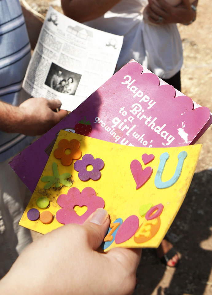 Washington television reporter Rebecca Cooper, right, sorts through a stack of cards and letter as she selects a few and reads them aloud to Nathan Kriesel, left, and his wife, Amber, whose hand is shown holding cards. Amber and Nathan Kriesel and their  three daughters survived the May 20 tornado, but their home at 601 SW 6 in Moore, and most of their possessions, were destroyed or scattered with the winds.  On Saturday, July 13, 2013, the couple brought their daughters to the site where their home once stood.  Nothing remains except dirt and sand. The foundation, driveway and sidewalks are piled about five-feet high next to the curb on 6th Street. Their neighborhood is practically.  A reporter from a Washington D.C. television station met the Kriesel family   in their former yard to return to them a large manila envelope filled with  sentimental items, including family letters and cards,   and daughter Zoe's artwork, that had been salvaged from the ruins in the days after the twister demolished their home.  Nathan and Amber expressed  gratitude for  special keepsakes  that have been located in the days and weeks following the storm and since have been returned to them-- Amber's locket, Nathan's high school soccer jacket and today,  the family's letters and cards dating back decades, from parents, loved ones, friends and  grandparents who are now deceased.     Photo  by Jim Beckel, The Oklahoman.