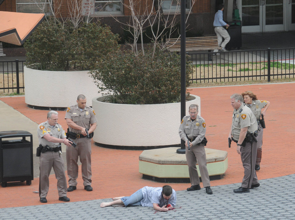 In this photo provided by John Fancher of the Tulsa City-County Library, sheriff's deputies surround a man who was wounded in an exchange of gunfire with law enforcement officers on the plaza in between the library and the Tulsa County Courthouse in Tulsa, Okla. on Wednesday, March 7, 2012. The shooter, a sheriff's deputy, and a bystander were wounded during the exchange, police said. (AP Photo/Tulsa City-County Library, John Fancher) MANDATORY CREDIT ORG XMIT: NY211