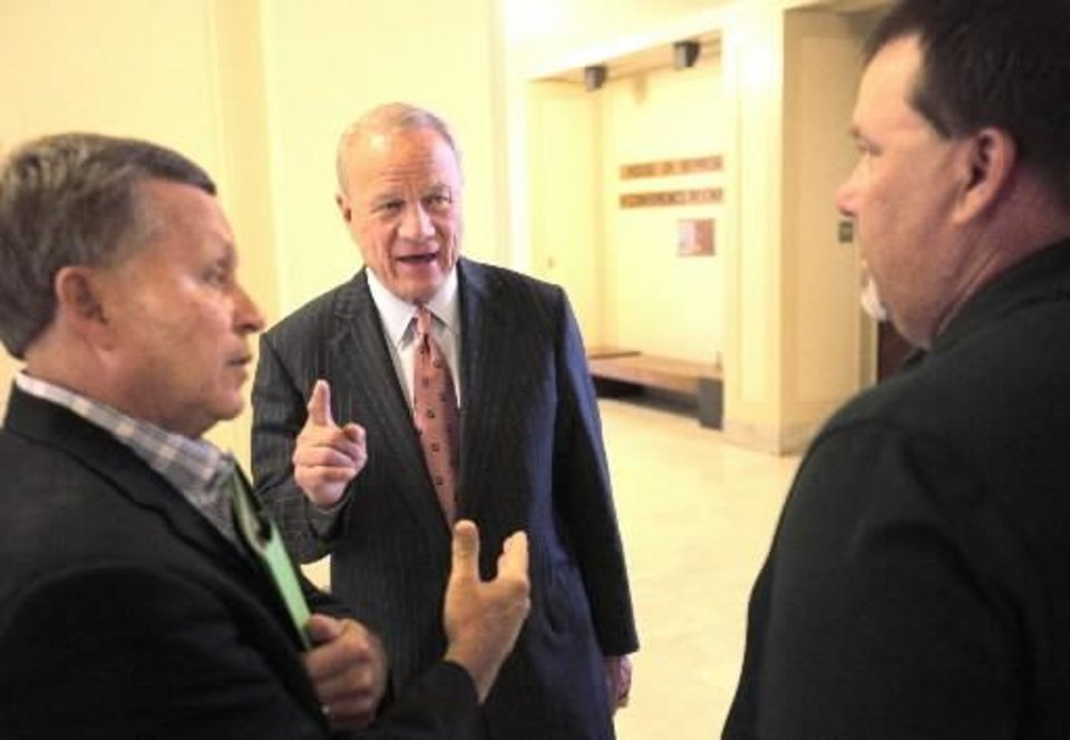 Barry Switzer, center, talks with Ernest Clark, a concerned citizen, left, and Kim Longest with the OFBCA (Oklahoma Football Coaches Association), right, at the state Capitol during the hearing on OSSAA and high school sports, Tuesday, September 17, 2013. Longest testified during the hearing. Photo by David McDaniel,