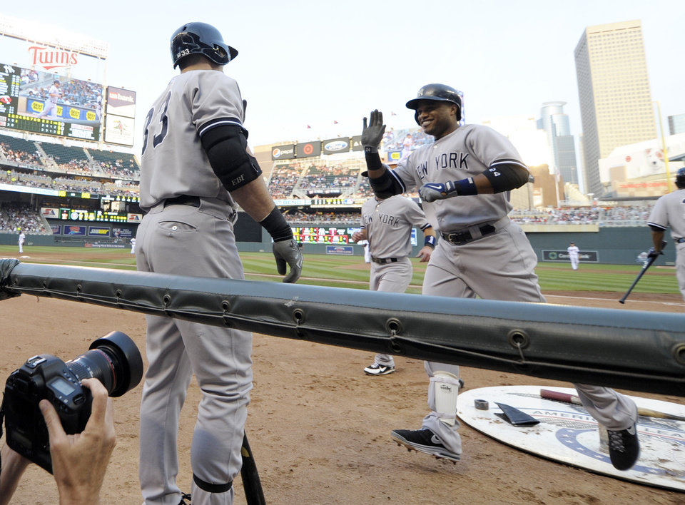 Photo - New York Yankees' Robinson Cano, right, is all smiles as he reaches the dugout after his second home run of the game in the third inning of a baseball game, Monday, July 1, 2013 in Minneapolis. (AP Photo/Jim Mone)