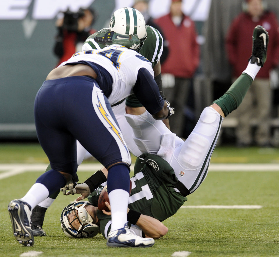 New York Jets quarterback Greg McElroy, bottom, is sacked by San Diego Chargers defensive end Corey Liuget, front left, during the second half of an NFL football game on Sunday, Dec. 23, 2012, in East Rutherford, N.J. The Chargers won 27-17. (AP Photo/Bill Kostroun)