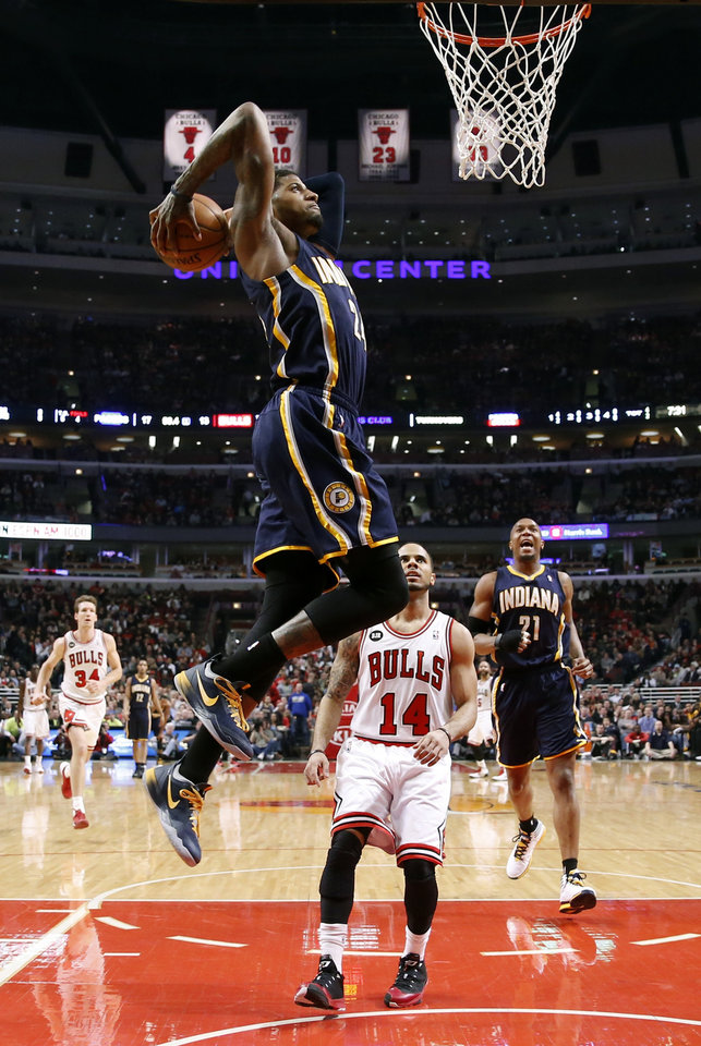 Photo - Indiana Pacers forward Paul George dunks the ball over Chicago Bulls guard D.J. Augustin (14) as David West (21) watches during the first half of an NBA basketball game Monday, March 24, 2014, in Chicago. (AP Photo/Charles Rex Arbogast)