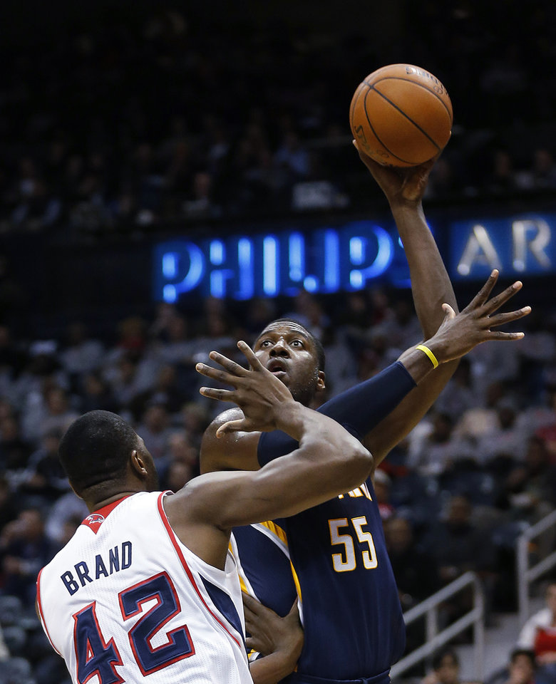 Photo - Indiana Pacers center Roy Hibbert (55) takes a shot against Atlanta Hawks power forward Elton Brand (42) in the first  half of an NBA basketball game, Tuesday, Feb. 4, 2014, in Atlanta. (AP Photo/John Bazemore)
