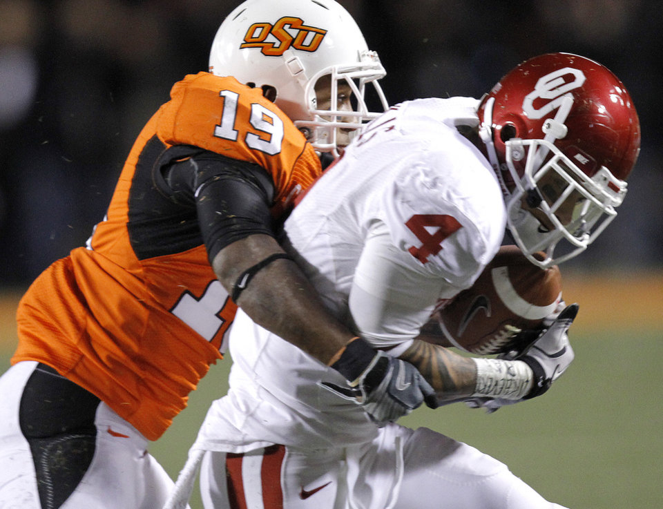 Photo - Oklahoma State's Brodrick Brown (19) brings down Oklahoma's Kenny Stills (4) during the Bedlam college football game between the University of Oklahoma Sooners (OU) and the Oklahoma State University Cowboys (OSU) at Boone Pickens Stadium in Stillwater, Okla., Saturday, Nov. 27, 2010. Photo by Chris Landsberger, The Oklahoman