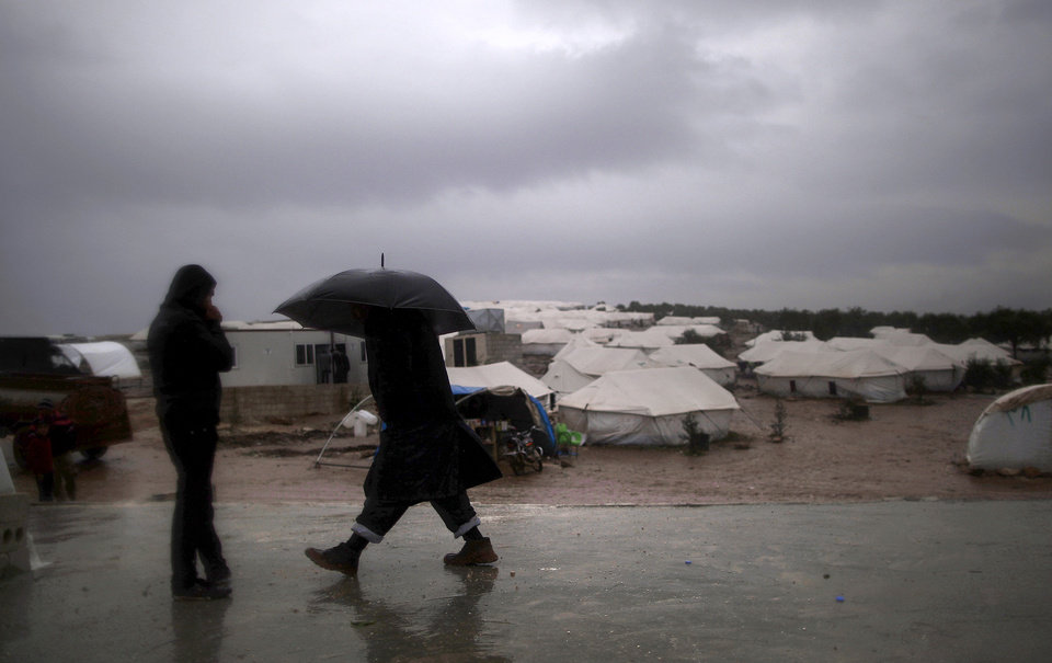 Photo - A Syrian man, who fled his home with his family, holds an umbrella to avoid the rain while walking back to his tent in a camp for the displaced in the village of Atmeh, Syria, Tuesday, Dec. 18, 2012. (AP Photo/Muhammed Muheisen)