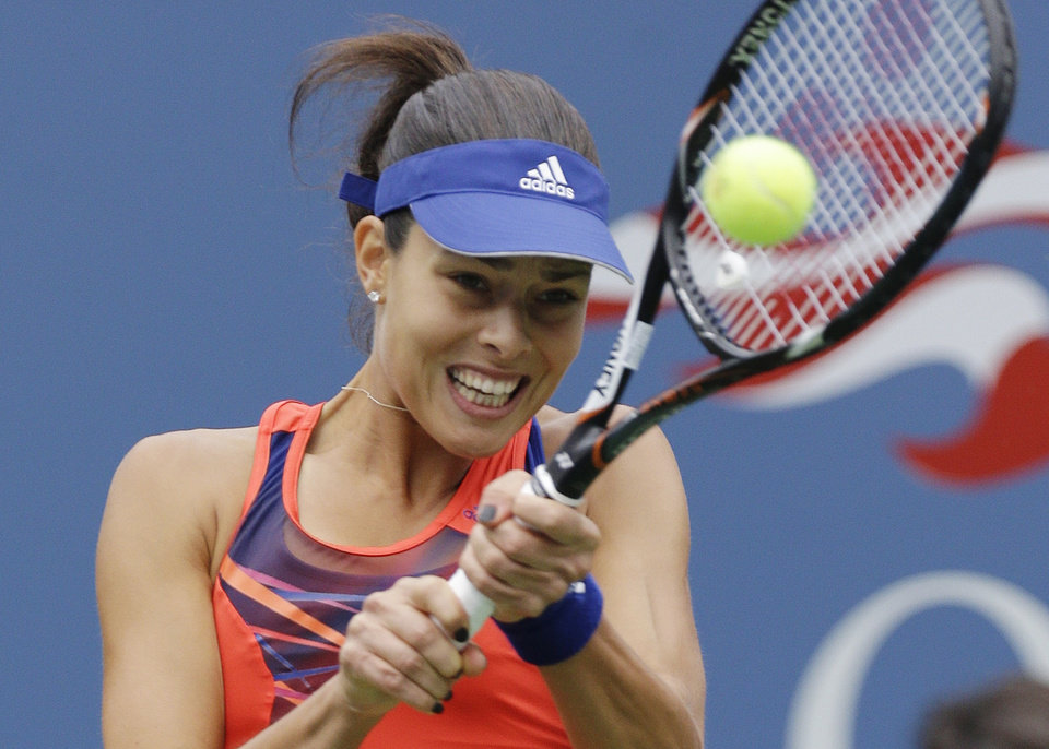 Photo - Ana Ivanovic, of Serbia, returns a shot to Victoria Azarenka, of Belarus, during the quarterfinals of the 2013 U.S. Open tennis tournament, Tuesday, Sept. 3, 2013, in New York. (AP Photo/Julio Cortez)