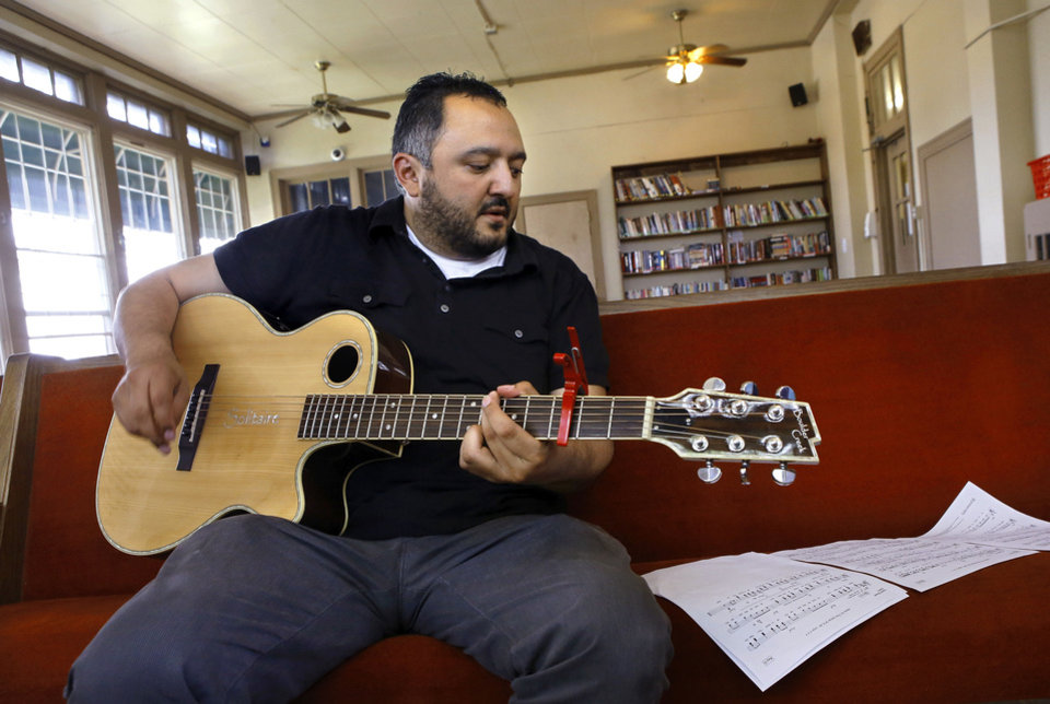 Photo - David Flores, a faculty member at Hillsdale Free Will Baptist College in Moore, strums his guitar during a rehearsal for the new Jesus House choir at the homeless shelter, 1335 W Sheridan. Photo by Jim Beckel, The Oklahoman   Jim Beckel