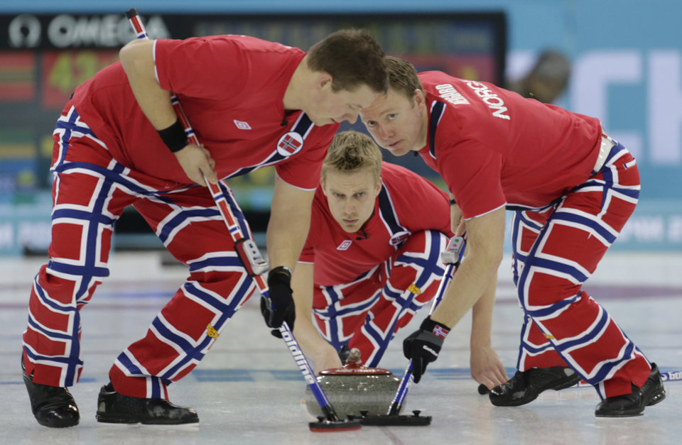 Photo - Norway's Christoffer Svae, left, and Torger Nergaard, sweep ahead of the stone delivered by Haavard Vad Petersson during men's curling competition against Sweden at the 2014 Winter Olympics, Thursday, Feb. 13, 2014, in Sochi, Russia. (AP Photo/Robert F. Bukaty)
