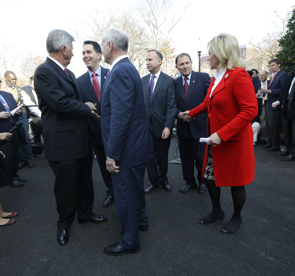 Photo - Members of the National Governors Association (NGA) Executive Committee, from left, Arkansas Gov. Mike Beebe; Wisconsin Gov. Scott Walker; Minnesota Gov. Mark Dayton; Chairman, Delaware Gov. Jack Markell; Utah Gov. Gary Herbert; and Vice Chair Oklahoma Gov. Mary Fallin, leave together after speaking to members of the media outside the West Wing of the White House in Washington, Tuesday, Dec. 4, 2012, following their meeting with President Barack Obama regarding the fiscal cliff. (AP Photo/Pablo Martinez Monsivais)