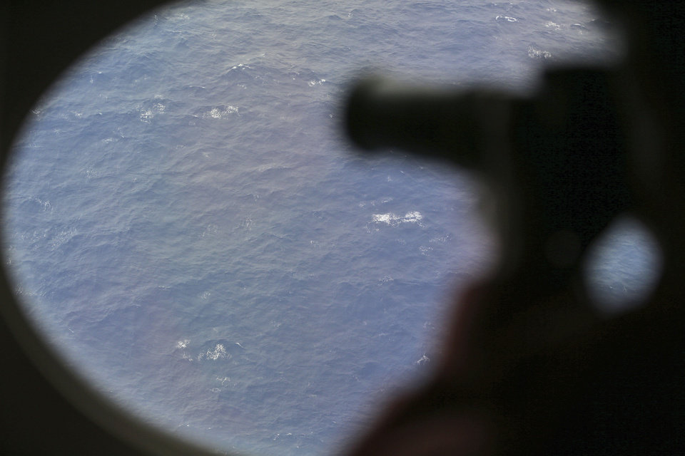 Photo - An observer on a Japan Coast Guard Gulfstream aircraft takes photos out of a window while searching for the missing Malaysia Airlines Flight MH370 in Southern Indian Ocean, near Australia, Tuesday, April 1, 2014. Bad weather and poor visibility caused the search to be called off early with the coast guard plane only completing one of its three 210 nautical mile legs. (AP Photo/Rob Griffith, Pool)
