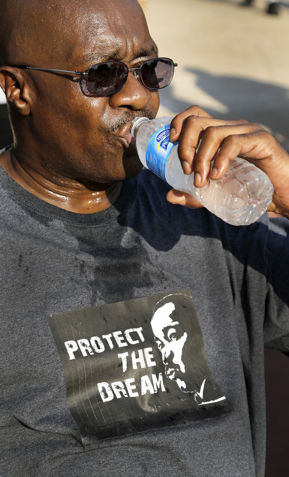"Ali Canada, one of the organizers of Saturday's march, drinks cold water after completing the walk from Stiles Park. Canada, who is from Tulsa, represented the Northeastern Oklahoma Coalition of Black Trade Unions. A diverse crowd of about  300 people rallied on the north side of the State Capitol Saturday morning, Aug. 24, 2013, to commemorate the upcoming 50th anniversary of the  1963 Civil Rights March on Washington.   Most of the crowd marched more than a mile from Stiles Park,  walking up Lincoln Blvd., to the statehouse. Many  in the crowd carried signs or banners, and some wore shirts bearing images of slain civil rights leader Martin Luther King Jr., who delivered his impassioned  oratory to a crowd of nearly 250,000 on the Washington Mall on Aug. 28, 1963.  At the time,  it was the largest demonstration ever seen in the nation's capital. King's remarks to the crowd, now known as the ""I Have A Dream"" speech, brought a national focus to the civil rights struggle in America and is credited with being a large influence to secure enough votes in Congress for the passage of the Civil Rights Act the following year.    Photo  by Jim Beckel, The Oklahoman."
