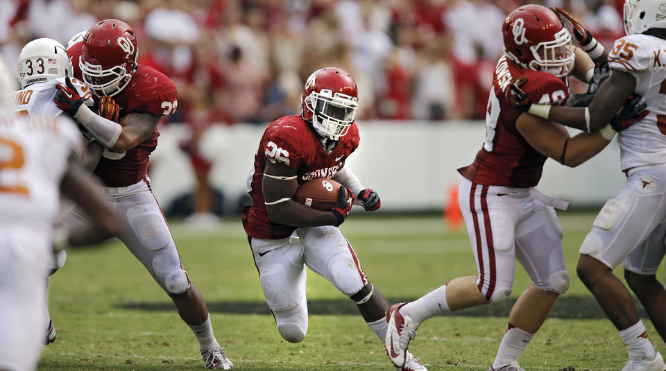 Photo - OU's Damien Williams (26) runs through the gap during the Red River Rivalry college football game between the University of Oklahoma (OU) and the University of Texas (UT) at the Cotton Bowl in Dallas, Saturday, Oct. 13, 2012. Photo by Chris Landsberger, The Oklahoman