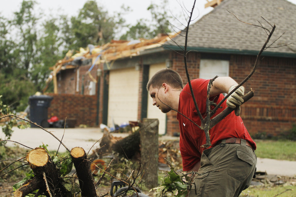 Cliff Holman tosses away cuttings as he works on a damaged tree in the Dripping Springs Estates Saturday, May 15, 2010. Saturday hundreds of volunteers went into areas that had been affected by last week's tornadoes to help clear debris. Photo by Doug Hoke, The Oklahoman.
