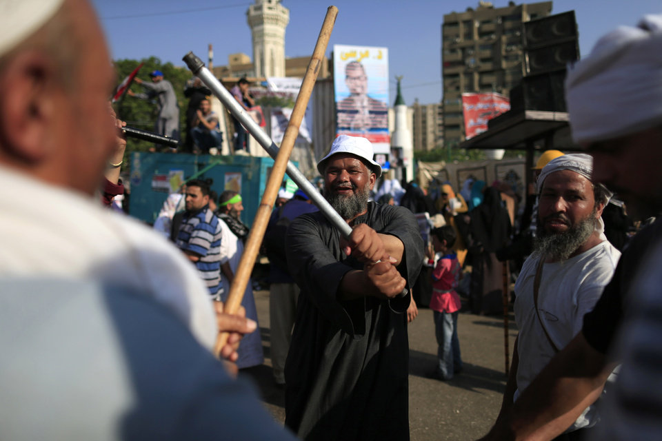 Supporters of Egypt\'s Islamist President Mohammed Morsi dance with sticks during a rally, in Nasser City, Cairo, Egypt, Thursday, July 4, 2013. The chief justice of Egypt\'s Supreme Constitutional Court was sworn in Thursday as the nation\'s interim president, taking over hours after the military ousted the Islamist President Mohammed Morsi. Adly Mansour took the oath of office at the Nile-side Constitutional Court in a ceremony broadcast live on state television. According to military decree, Mansour will serve as Egypt\'s interim leader until a new president is elected. A date for that vote has yet to be set. (AP Photo/Hassan Ammar)