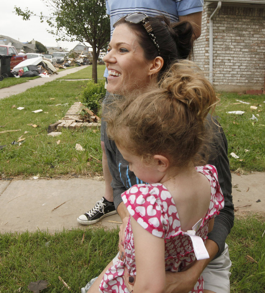 Photo - Briarwood Elementary School 5th grade teacher Robin Dziedzic hugs a small child who dropped by to offer her water while she talks about her experiences when her school was destroyed by the May 20th tornado in Moore, OK, Saturday, May 25, 2013,  Photo by Paul Hellstern, The Oklahoman