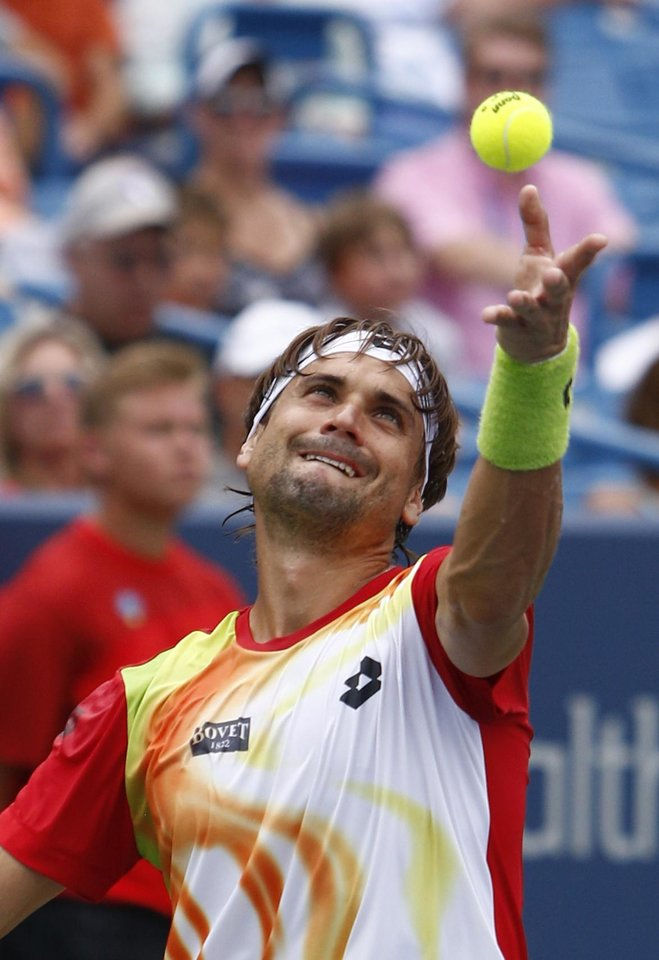 Photo - David Ferrer, from Spain, serves to Julien Benneteau, from France, during a semifinal match at the Western & Southern Open tennis tournament, Saturday, Aug. 16, 2014, in Mason, Ohio. (AP Photo/David Kohl)