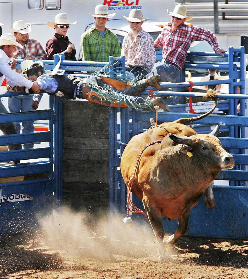 Landon Parrish, from Kayenta, AZ, holds on the shoot rail as the bull he was trying to ride gets out of the gate early at the  International Finals Youth Rodeo in Shawnee, Wednesday,  July 15 , 2009.  Photo By David McDaniel, The Oklahoman