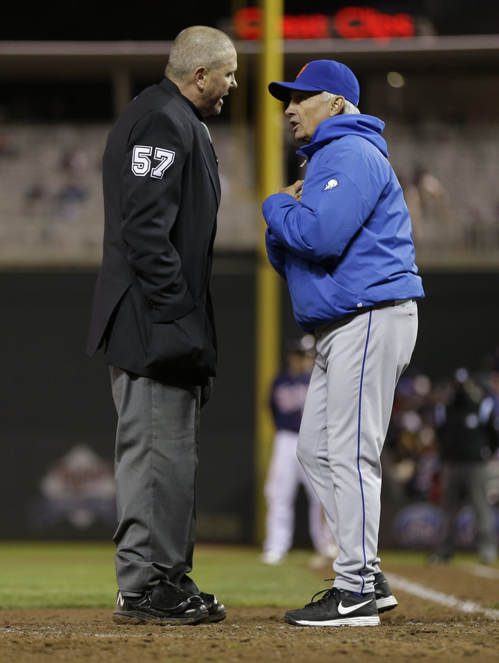 Photo - New York Mets manager Terry Collins, right, pleads his case with plate umpire Mike Everitt after Minnesota Twins' Justin Morneau was called safe on a play at home, scoring on a two-run single by Ryan Doumit in the fifth inning of a baseball game on Friday, April 12, 2013, in Minneapolis. (AP Photo/Jim Mone)