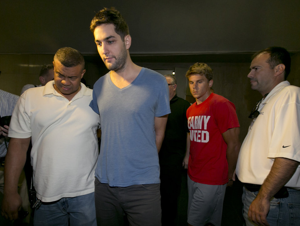 Photo - Daniel Petryszyn, second left, and Bryan Caputo, third left, are escorted to their arraignment proceedings in New York state Supreme Court, Wednesday, July 23, 2014. They are two of six people who were indicted Wednesday in an international ring that took over more than 1,600 StubHub users' accounts and fraudulently bought tickets to such prime events as Jay-Z and Elton John concerts and Broadway shows like