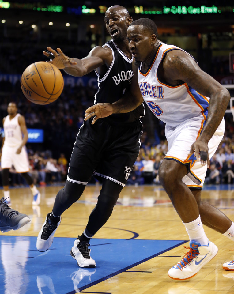 Photo - Thunder's Kendrick Perkins (5) and Brooklyn's Kevin Garnett fight for the ball in the first half of an NBA basketball game where the Oklahoma City Thunder were defeated 95-93 by the Brooklyn Nets at the Chesapeake Energy Arena in Oklahoma City, on Thursday, Jan. 2, 2014. Photo by Steve Sisney The Oklahoman