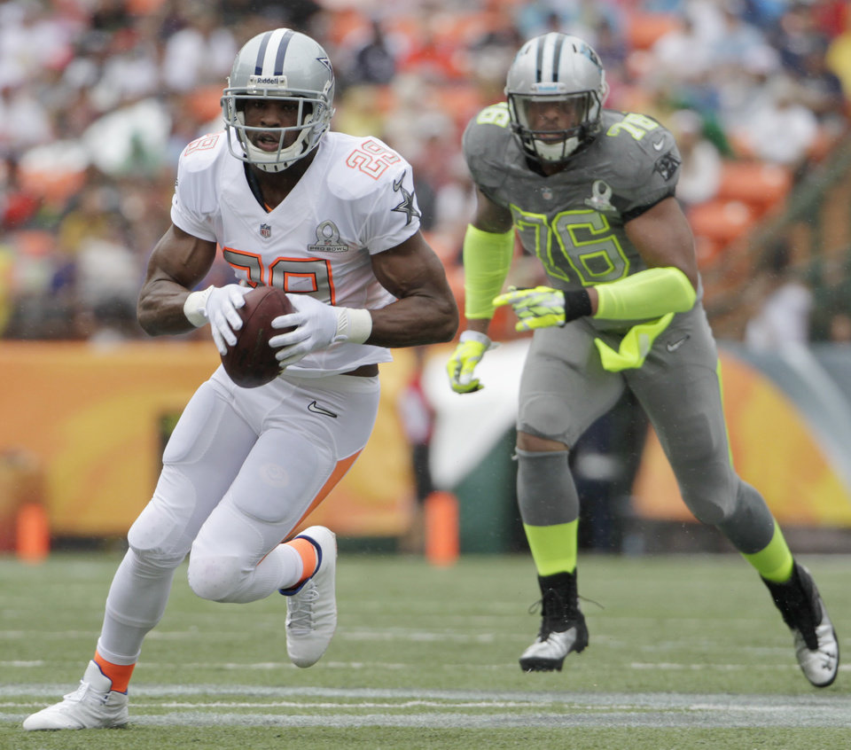 Photo - Dallas Cowboys running back DeMarco Murray (29) of Team Rice runs with the football after catching a pass in the first quarter quarter of the NFL Pro Bowl football game Sunday, Jan. 26, 2014, in Honolulu. Carolina Panthers defensive end Greg Hardy (76) of Team Sanders looks on during the play. (AP Photo/Eugene Tanner)