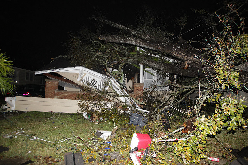 Photo - A house in the Midtown section of Mobile, Ala. is damaged after a tornado touched down Tuesday, Dec. 25, 2012. A Christmas Day twister outbreak left damage across the Deep South while holiday travelers in the nation's much colder midsection battled sometimes treacherous driving conditions from freezing rain and blizzard conditions. (AP Photo/AL.com, Mike Kittrell)  MAGS OUT