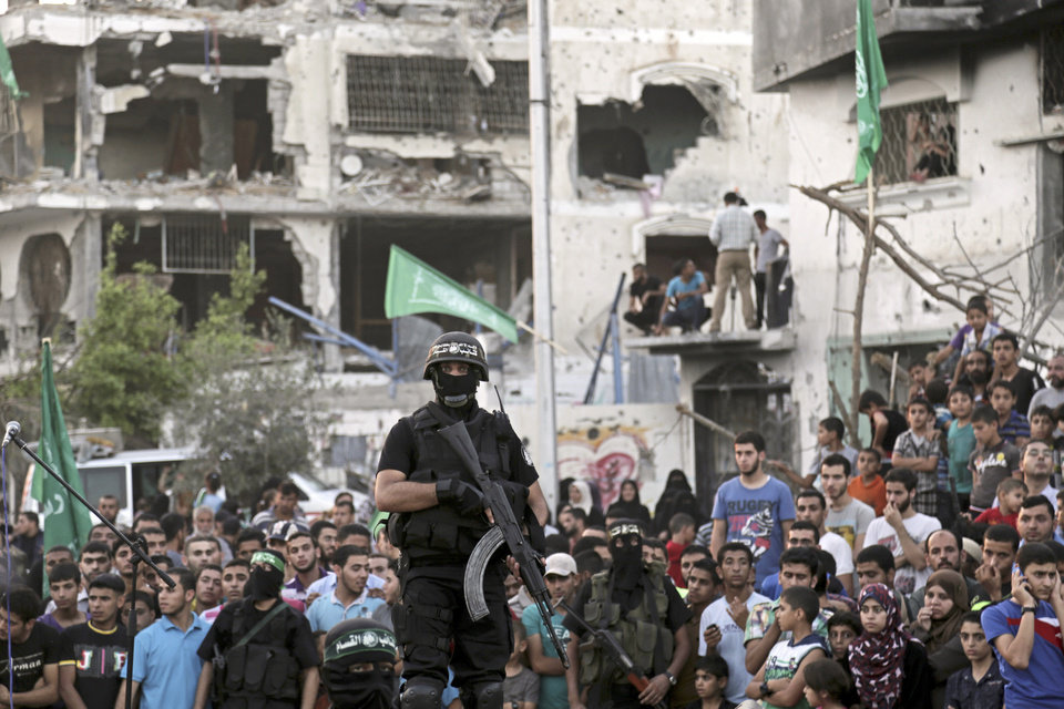 Photo - Palestinian masked militants of Izzedine al-Qassam Brigades, military wing of Hamas, and their supporters  celebrate during a victory rally at the debris of destroyed houses in Shijaiyah, neighborhood of Gaza City, in the northern Gaza Strip, Wednesday, Aug. 27, 2014. An open-ended cease-fire between Israel and Palestinian militants in the Gaza Strip was holding Wednesday. (AP Photo/Adel Hana)