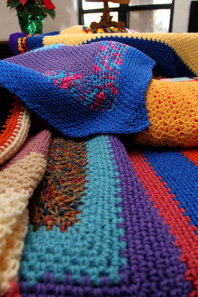 Colorful afghans made by artist Janet Carpenter are on display at an arts market Saturday sponsored by West Wind Unitarian Universalist Congregation in Norman. PHOTO BY HUGH SCOTT, FOR THE OKLAHOMAN <strong>HUGH SCOTT</strong>