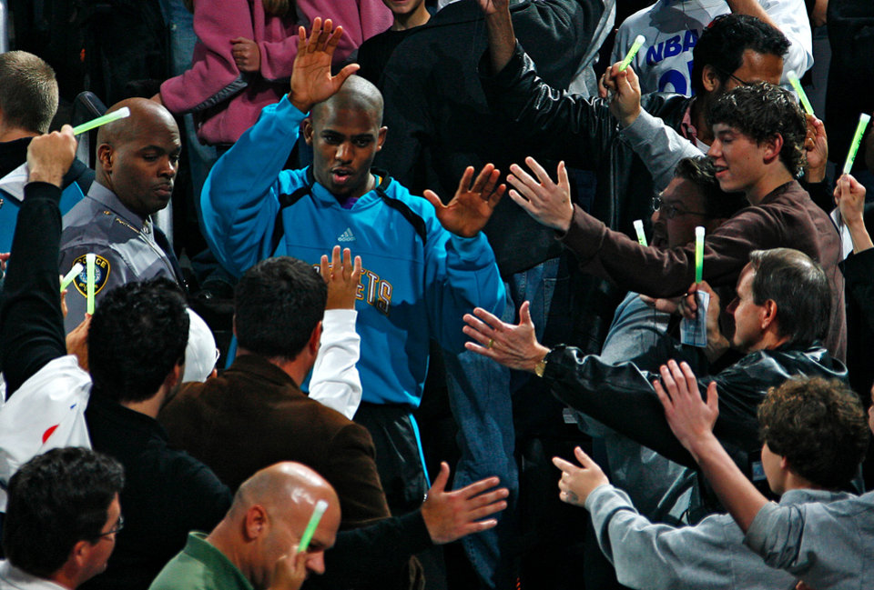 Photo - FINAL REGULAR SEASON HOME GAME: The Hornets' Chris Paul, center, slaps hands with the fans as he makes his way through the stands before the start of the NBA basketball game between the New Orleans/Oklahoma City Hornets and the Denver Nuggets at the Ford Center in Oklahoma City, Friday, April 13, 2007. By Nate Billings, The Oklahoman  ORG XMIT: KOD