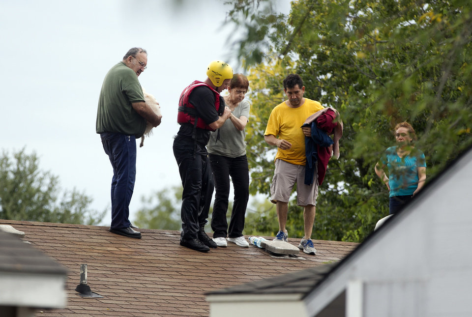 Photo - People are rescued from a home's rooftop  in southeast Austin, Texas, on Thursday, Oct. 31, 2013. Heavy overnight rains brought flooding to the area. The National Weather Service said more than a foot of rain fell in Central Texas, including up to 14 inches in Wimberley, since rainstorms began Wednesday.  (AP Photo/The Austin American-Statesman, Deborah Cannon) AUSTIN CHRONICLE OUT, COMMUNITY IMPACT OUT, INTERNET MUST CREDIT PHOTOGRAPHER AND STATESMAN.COM, NO SALES