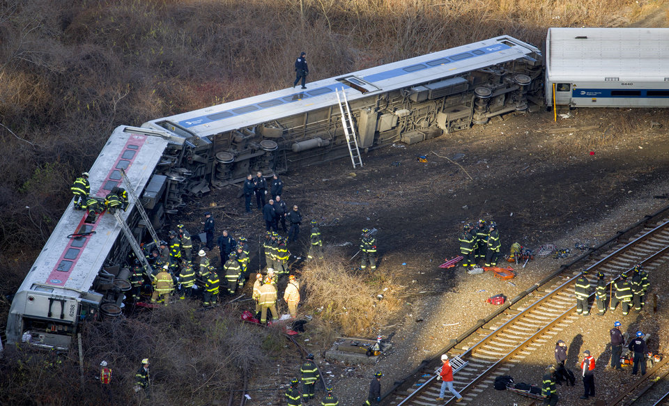 Photo - First responders work the scene of a derailment of a Metro-North passenger train in the Bronx borough of New York Sunday, Dec. 1, 2013. The train derailed on a curved section of track in the Bronx on Sunday morning, coming to rest just inches from the water and causing multiple fatalities and dozens of injuries, authorities said. Metropolitan Transportation Authority police say the train derailed near the Spuyten Duyvil station. (AP Photo/Craig Ruttle)