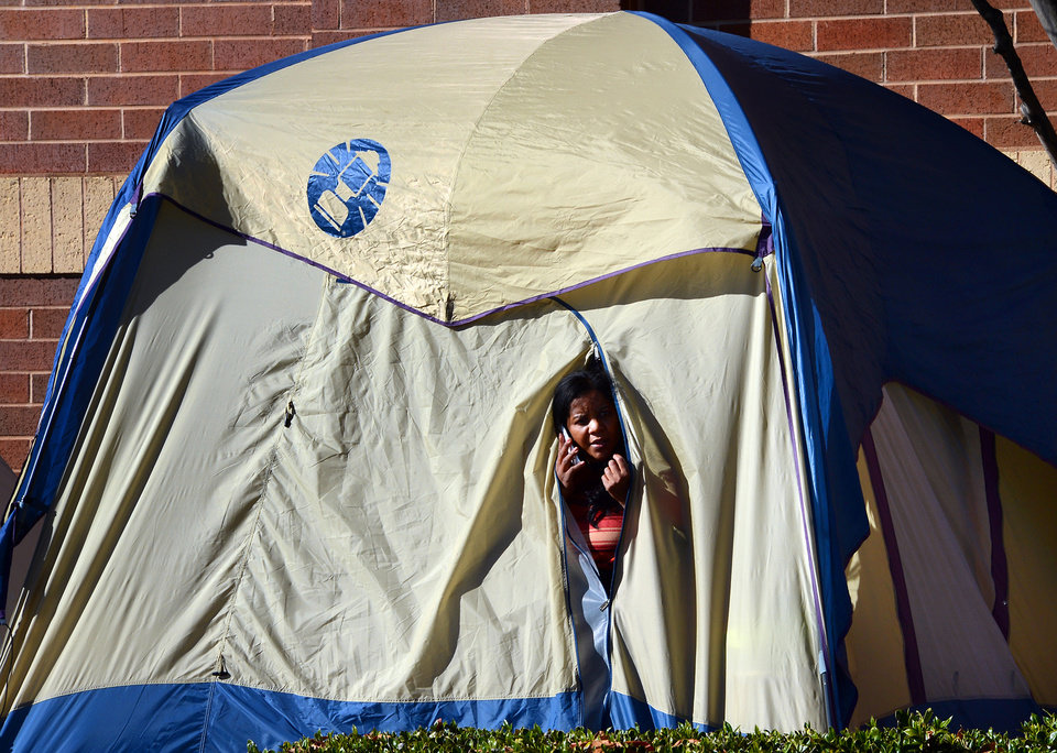 Photo -   Beth Collins, of Garner peeks out from her tent on Thanksgiving morning as she waits in line in front of the Best Buy in Garner, N.C. Stores typically open in the wee hours of the morning on the day after Thanksgiving known as Black Friday, named for the period when stores traditionally turn a profit for the year. But Black Friday openings have crept earlier and earlier over the past few years. Now, stores from Wal-Mart to Toys R Us are opening their doors on Thanksgiving evening, hoping Americans will be willing to shop soon after they finish their pumpkin pie. (AP Photo/The News & Observer , Chuck Liddy)