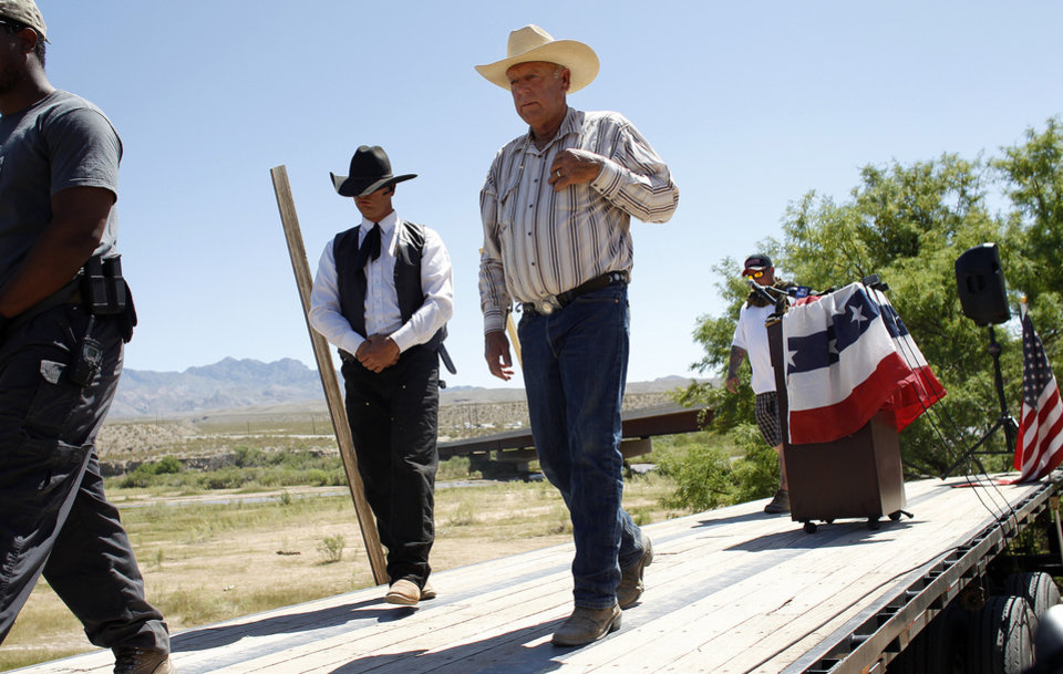 Photo - Rancher Cliven Bundy, center, walks off stage after speaking at a news conference near Bunkerville, Nev., Thursday, April 24, 2014. Bundy, a Nevada rancher who became a conservative folk hero for standing up to the government in a fight over grazing rights, lost some of his staunch defenders Thursday after wondering aloud whether blacks might have had it better under slavery. (AP Photo/Las Vegas Review-Journal, John Locher)