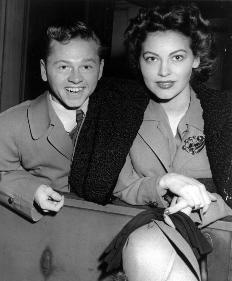 Photo - FILE - Mickey Rooney and wife, Ava Gardner, arrive in New York in January 1942, en route to Boston where Rooney is to appear at a Red Cross benefit. Rooney, a Hollywood legend whose career spanned more than 80 years, has died. He was 93. Los Angeles Police Commander Andrew Smith said that Rooney was with his family when he died Sunday, April 6, 2014, at his North Hollywood home. (AP Photo/File)