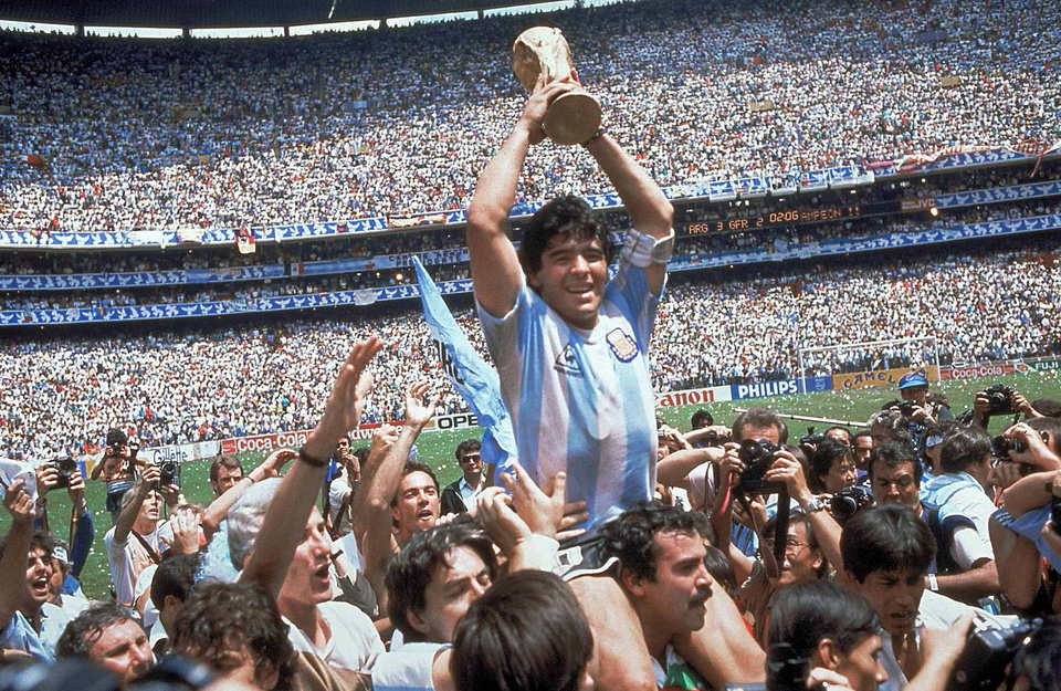 Photo - FILE - In this June 29, 1986, file photo, Diego Maradona, holds up the trophy, after Argentina beat West Germany 3-2 in their World Cup soccer final match, at the Atzeca Stadium, in Mexico City. On this day: Maradona leads Argentina to its second World Cup triumph. (AP Photo/Carlo Fumagalli, File)