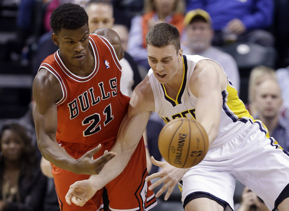 Photo - Chicago Bulls forward Jimmy Butler, left, knocks the ball away from Indiana Pacers forward Tyler Hansbrough during the first half of an NBA basketball game in Indianapolis, Monday, Feb. 4, 2013. (AP Photo/Michael Conroy)