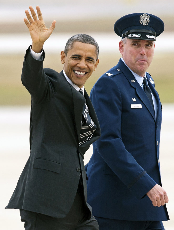 Photo -   President Barack Obama, accompanied by Air Force Col. Michael A. Minihan, commander, 89th Airlift Wing, waves as he walks to Air Force One at Andrews Air Force Base, Md., Thursday, Nov. 15, 2012, en route to New York to visit areas devastated by Superstorm Sandy. (AP Photo/Cliff Owen)