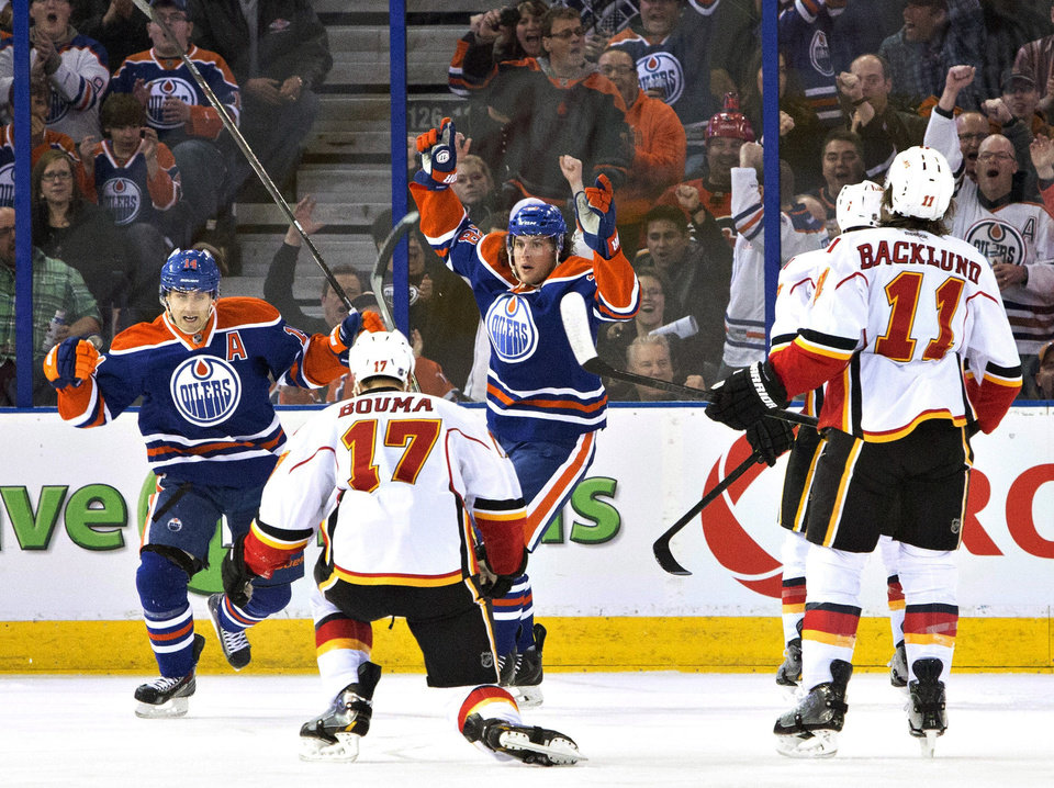 Photo - Calgary Flames' Lance Bouma (17), Mikael Backlund (11) and TJ Brodie watch as Edmonton Oilers' Jordan Eberle (14) and Ryan Jones (28) celebrate a goal during the first period of an NHL hockey game Saturday, March 22, 2014, in Edmonton, Alberta. (AP Photo/The Canadian Press, Jason Franson)