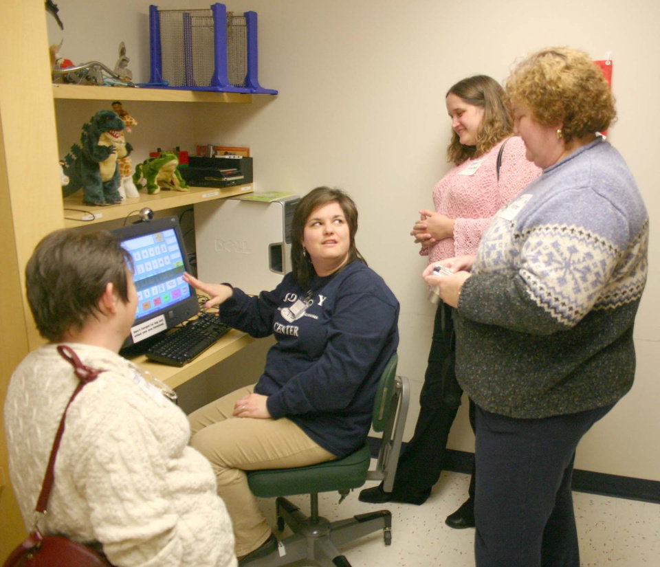 Reni Hanley (seated), director of communication disorders for the J. D. McCarty Center, demonstrates some of the new augmentative communications assessment equipment made possible through a grant for $7,524 from the Boeing Employee Community Fund. Representing the Boeing Employee Community Fund are (l-r) Janet Graber, Sharon Nicholson and Karen Mata.<br/><b>Community Photo By:</b> Greg Gaston<br/><b>Submitted By:</b> Greg,