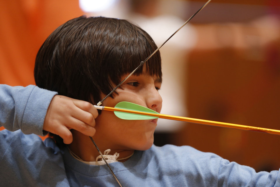 Photo - Pierson Majma, 9, pulls back his bow as he practices during an after-school archery class in Edmond. PHOTO BY BRYAN TERRY, THE OKLAHOMAN  BRYAN TERRY - THE OKLAHOMAN