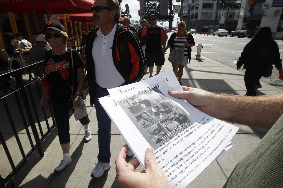 Bradley Meadows, friend of Los Angeles Dodgers fan Jonathan Denver, passes out fliers outside AT&T Park before the Giants' baseball game in San Francisco, Sunday, Sept. 29, 2013. Denver, 24, was fatally stabbed Wednesday during a melee following the Dodgers' game against the Giants. (AP Photo/Tony Avelar)