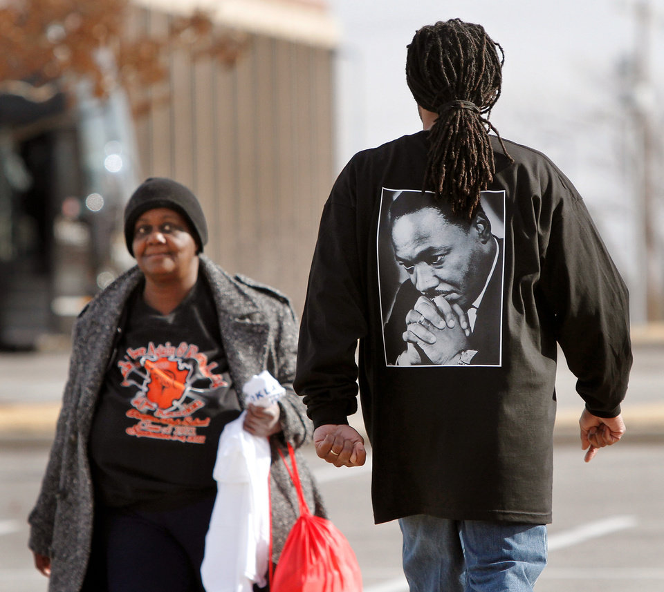 A woman walks past a man wearing a shirt with an image of Martin Luther King as he leaves the bell ringing ceremony at the Oklahoma History center; it is one of several events in the Oklahoma City area that allowed local residents to observe the national holiday honoring slain civil rights leader, Dr. Rev. Martin Luther King, Jr. on Monday, Jan. 16,  2012,    Photo by Jim Beckel, The Oklahoman
