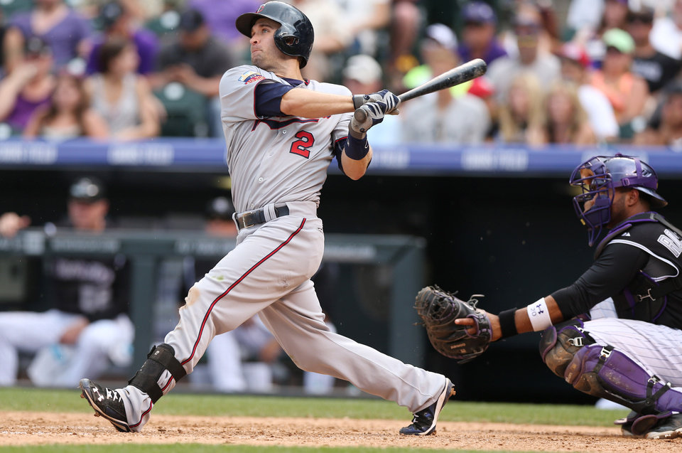 Photo - Minnesota Twins' Brian Dozier, left, follows the flight of his three-run home run as Colorado Rockies catcher Wilin Rosario looks on in the ninth inning of the Twins' 13-5 victory in an interleague baseball game in Denver on Sunday, July 13, 2014. Dozier hit a solo home run to lead off the eighth inning as well. (AP Photo/David Zalubowski)
