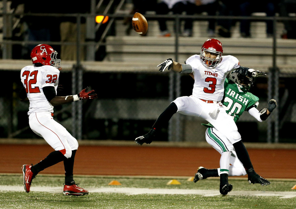 Photo - Titan Steven Thompson (3) deflects a pass intended for Bradley Roy (20) and knocks it into the hands of Nate Christmon (32) for an interception as the Bishop McGuinness Irish play the Carl Albert Titans in a Class 5A semi-final playoff game at Harve Collins Field on Friday, Nov. 23, 2012  in Norman, Okla. Photo by Steve Sisney, The Oklahoman